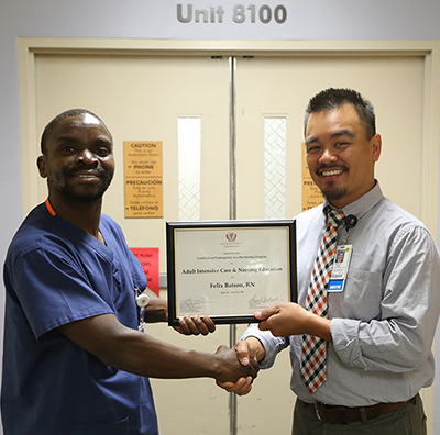 Derek Hidalgo, MBA, RN, BSN, director of patient care MICU/SICU/Neurology, right, presents Felix Batson, RN with a mentorship program certificate.