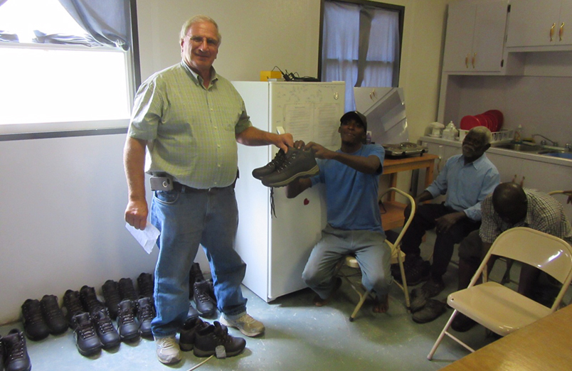 Pastor Carlson giving shoes to Haitians