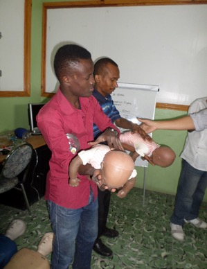 2 men learning CPR on baby