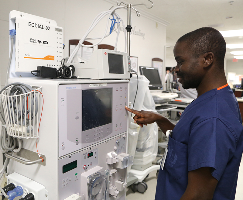 Felix Batson, RN, marvels at a dialysis machine, a device he has only read about.